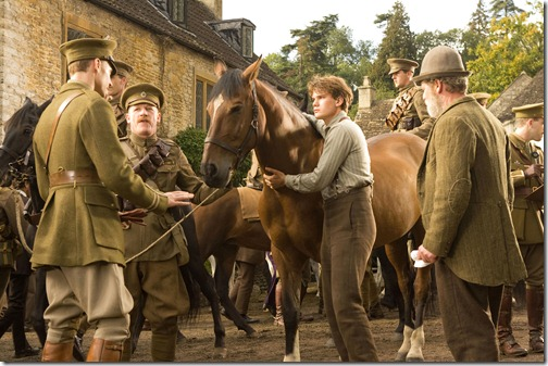 """WAR HORSE""..DM AC 33426R..Captain Nicholls (Tom Hiddleston, far left) and Sergeant Perkins (Geoff Bell) prepare to take Joey away with them. Albert (Jeremy Irvine, center) holds on to Joey defiantly while his father (Peter Mullan, right) looks on in this scene from DreamWorks Pictures' ""War Horse"". Director Steven Spielberg's epic adventure is set against a sweeping canvas of rural England and Europe during the First World War...Ph: Andrew Cooper, SMPSP..©DreamWorks II Distribution Co., LLC. ÊAll Rights Reserved."